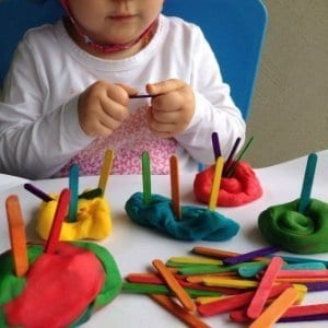 Child with colorful playdough and paddlepop sticks