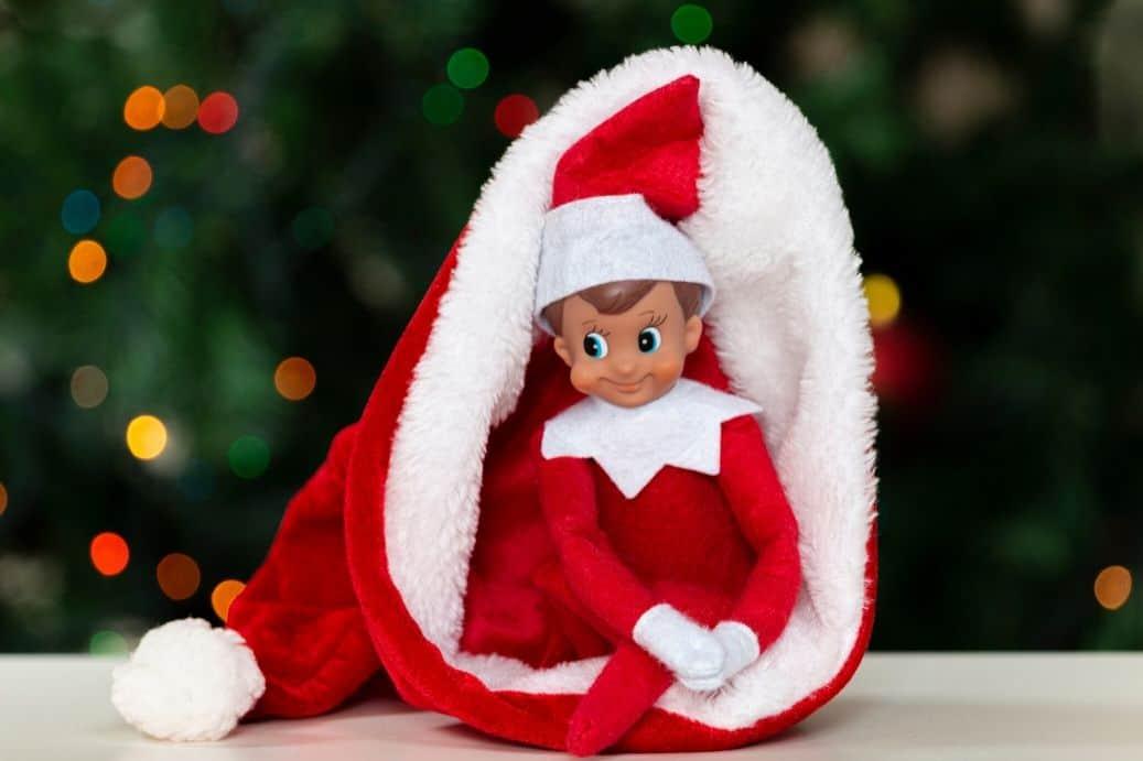 Elf on the Shelf hiding in a Santa hat